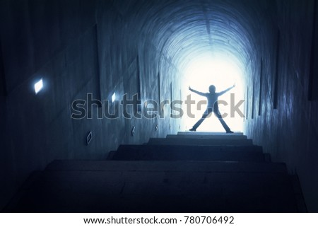 Silhouette of a woman on a ladder in a dark tunnel