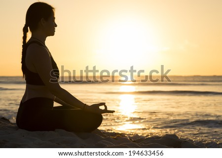 Silhouette of a woman practicing yoga by the beach at sunrise