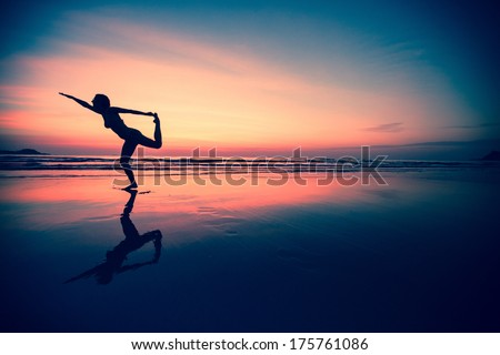 Silhouette of a woman practicing yoga on the beach at sunset. - stock photo