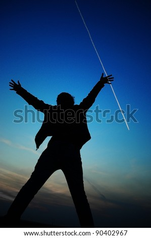 silhouette of a woman raising her arms out to the sky - stock photo