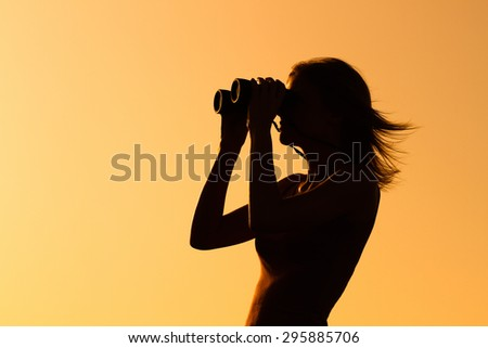 Silhouette of a woman standing and watching sunset with binoculars . Enjoying in sunset with binoculars  - stock photo