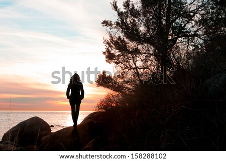 Silhouette of a woman standing in front of the gorgeous reddish sunset at the New England shoreline. - stock photo