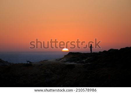 Silhouette of a woman standing on a cliff and looking at a sunset, with a beautifully colored orange sun going down in the ocean - stock photo