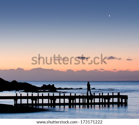 Silhouette of a woman walking on pier with moon in the sky - stock photo