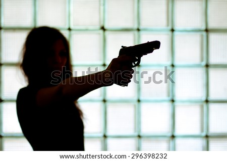 Silhouette of a woman with a gun on a glass wall background. - stock photo