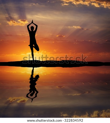 Silhouette of a woman Yoga in the evening. Woman doing Yoga at sunset
