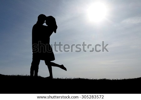 Silhouette of a young couple. Blue sky background. - stock photo