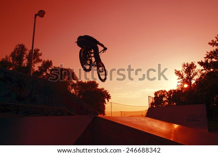 Silhouette of a Young cyclists to jump on the ramp  - stock photo