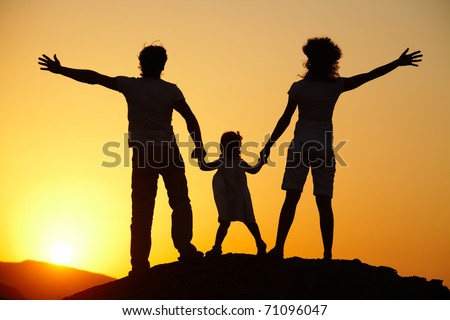 Silhouette of a young family with a child standing on a decline against the bright sun - stock photo