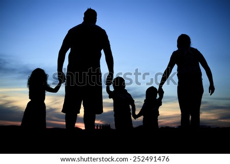 Silhouette of a young family with some childs standing - stock photo