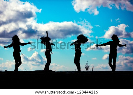 silhouette of a young girl dancing against a beautiful sky - stock photo