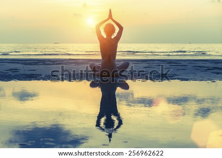 Silhouette of a young girl (with reflection in the water) practicing yoga on the beach during sunset. - stock photo