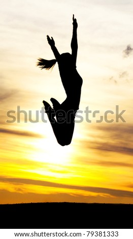 Silhouette of a young jumping woman against yellow sky with clouds at sunset