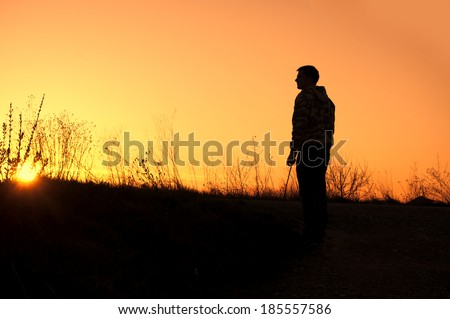 Silhouette of a young man at sunset - stock photo