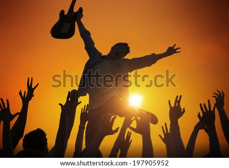 Silhouette of a Young Man Performing in Front of the Crowd - stock photo
