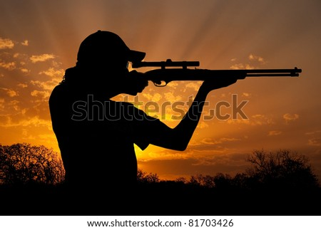 Silhouette of a young man with ponytail shooting against dramatic sunset sky