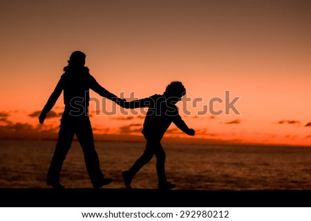 Silhouette of a young mother and her son walking along apier in front of a red sunset in the sky on a summer day