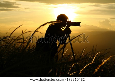 Silhouette of a young photographer during the sunset. - stock photo