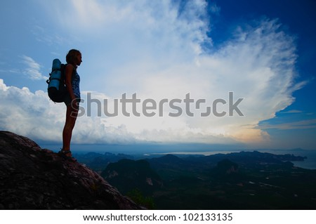 Silhouette of a young tourist with backpack standing on top of a mountain