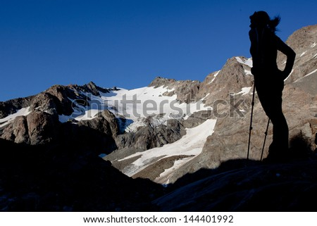 Silhouette of a young woman in alpine scenery - stock photo