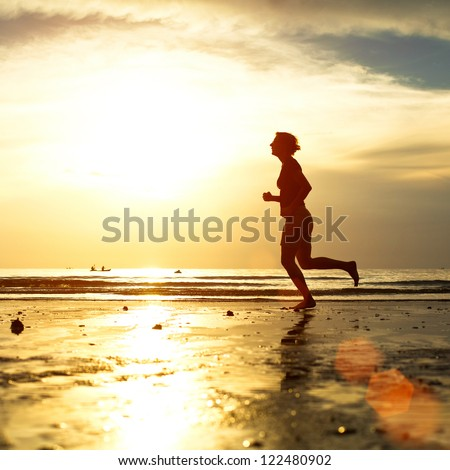 Silhouette of a young woman jogger at sunset on the seashore - stock photo