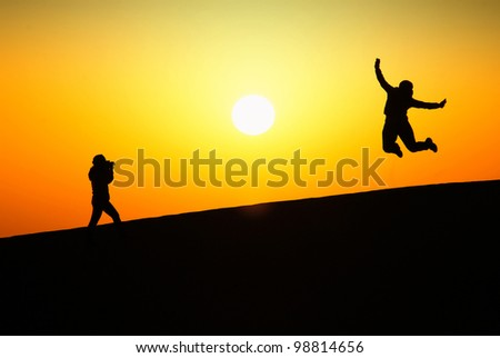 Silhouette of a young woman jumping and a photographer at the sunset on a dune. - stock photo