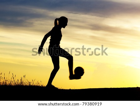 Silhouette of a young woman playing football  against yellow sky with clouds - stock photo