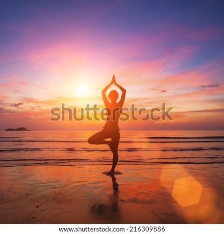 Silhouette of a young woman practicing yoga in the rays of the surrealist sunset at the seaside. - stock photo