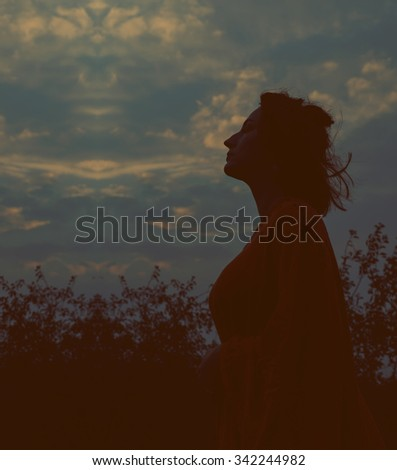 Silhouette of a young woman relaxing on a beautiful sunset. Woman enjoying nature sunset. Serious sad woman. Silhouette of the woman standing lonely at the field during beautiful sunset. Retro image.