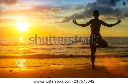 Silhouette of a young woman yoga exercise on the ocean beach at sunset time. - stock photo