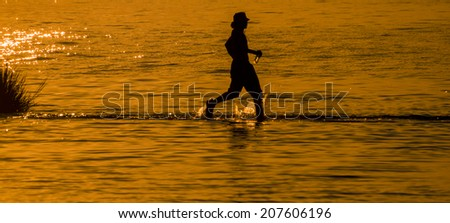 Silhouette of a youth running in the shallow waters of the Indian River Inlet (Delaware). - stock photo