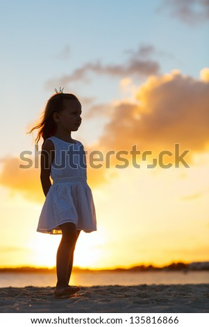 Silhouette of adorable little girl on a beach at sunset - stock photo