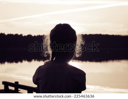 Silhouette of adorable little girl on the lake at sunset. Toned - stock photo