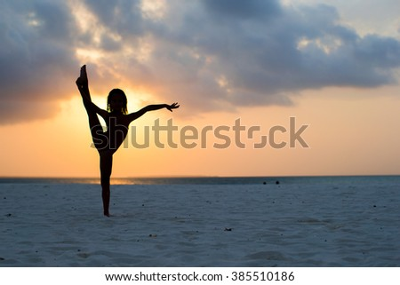Silhouette of adorable little girl on white beach at sunset