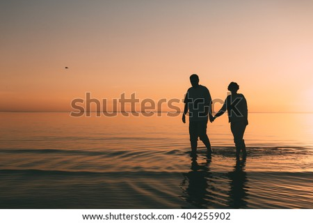 Silhouette of adult couple standing in the sea against a sunset. Evening photo. - stock photo