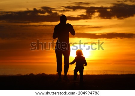 Silhouette of adult walking with child during sunset - stock photo