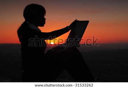Silhouette of African American Business Woman Working with Laptop during Sunset on top of Hill - stock photo