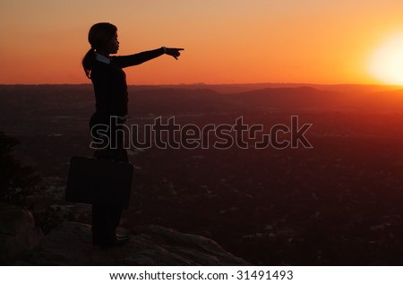 Silhouette of African American Woman Standing and Pointing Towards Skyline - stock photo