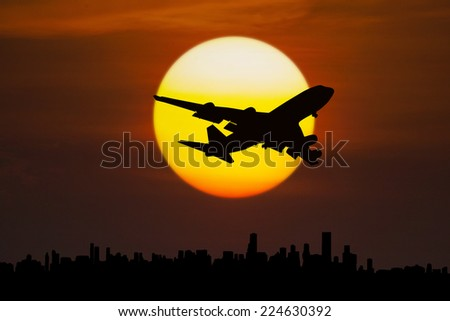 Silhouette of aircraft flying above city at dusk - stock photo