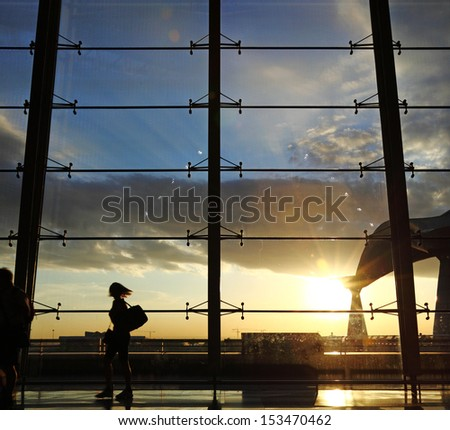 Silhouette of airline passengers in an airport lounge against an observation window with a surreal sunset in the horizon.