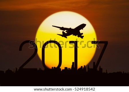 Silhouette of airplane flying in the sky above numbers 2017 and city with a golden sun, shot at sunset time
