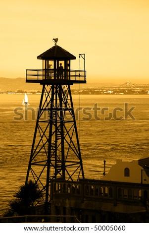Silhouette of Alcatraz Guard Tower, Bay Bridge in background. - stock photo