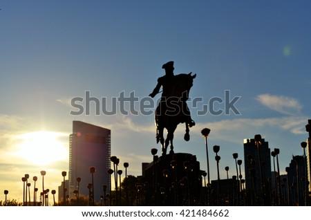 Silhouette of allium flowers and George Washington statue in Boston Public Garden - stock photo