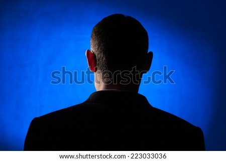 Silhouette of an adult male in his early forties wearing a jacket and shirt. - stock photo