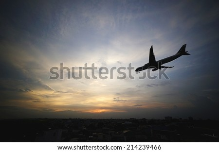silhouette of an aircraft preparing for landing at dramatic sunset in Tan Son Nhat Airport, Ho CHi Minh City, Vietnam. - stock photo