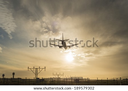 Silhouette of an airplane landing at dusk. - stock photo