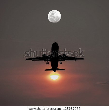 Silhouette of an airplane taking off against a fiery setting sun flying towards a full moon in the evening sky. - stock photo