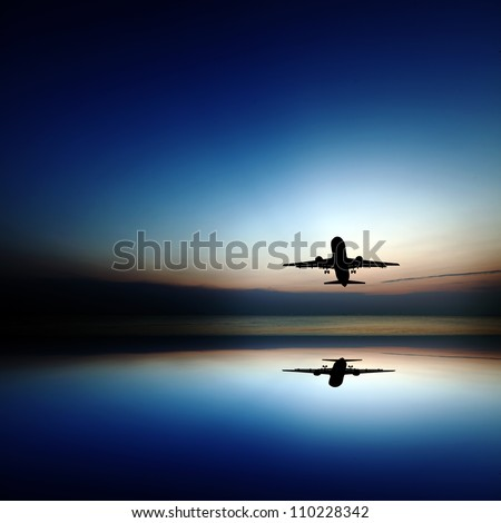 Silhouette of an airplane taking off into a surreal colorful evening sky with reflection.