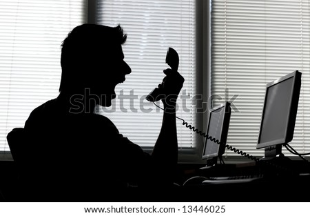 Silhouette of an angry man shouting into the phone receiver in his office - stock photo