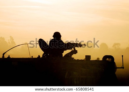 Silhouette of an army soldier preparing his tank and weapons at sunset. Concept photo of war ,military, army, armed forces, incursion,conflict ,firearm ,battle, attack.   - stock photo
